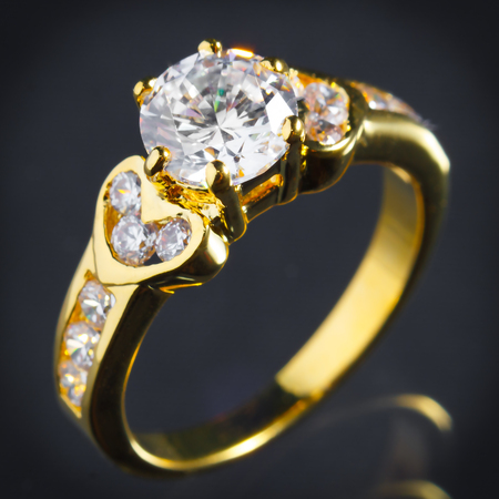 close up gold diamond ring on gray background, vignette effect