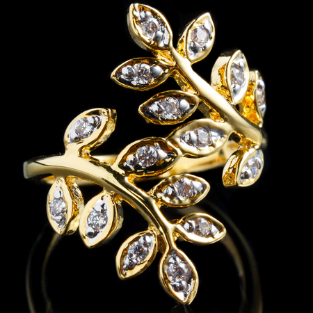 close up gold diamond ring with reflection
