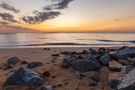 seascape during beautiful color sky at sunset with old rock with forground Stock Photo