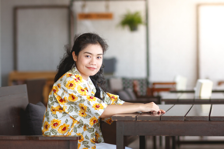 asian woman wear white t-shirt and yellow shirt sitting at wooden chair