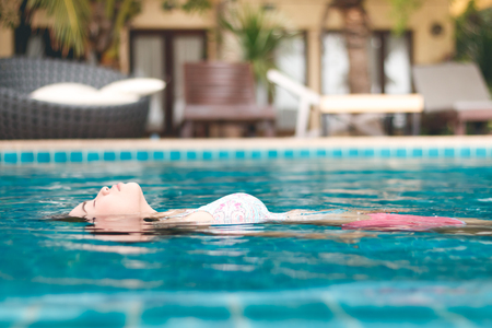 beauty asian woman in swimwear is pink and blue, in swimming pool