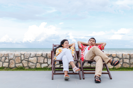 couple asian man and woman with yellow and red shirt sitting, beautiful sky background