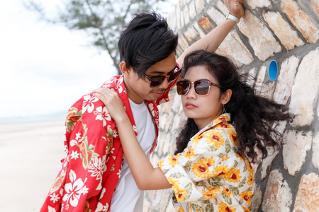 couple asian man and woman wear yellow and red shirt close up, beautiful sky background Stock fotó