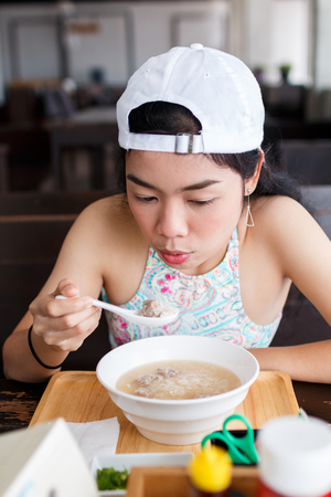beauty asian woman with white hat eatting food