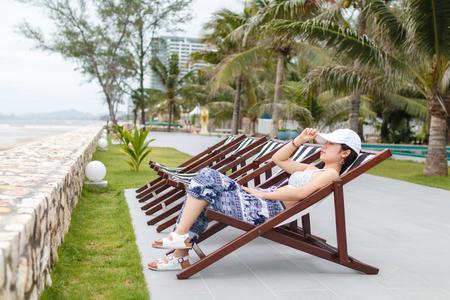 beauty asian woman lie on wooden chair side beach