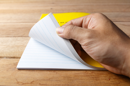 right hand open yellow emptry notebook on wooden background Stock fotó