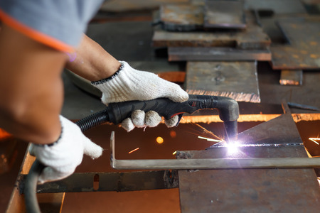 metal structure: worker cutting metal sheet with plasma in factory