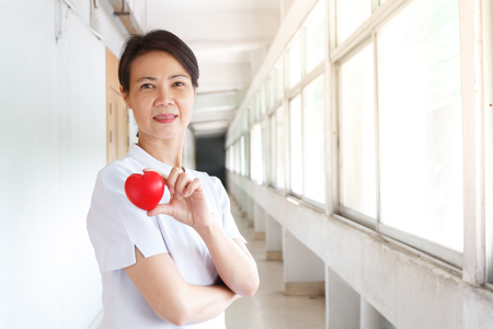 asian nurse in white uniform holding red heart beat with her hands
