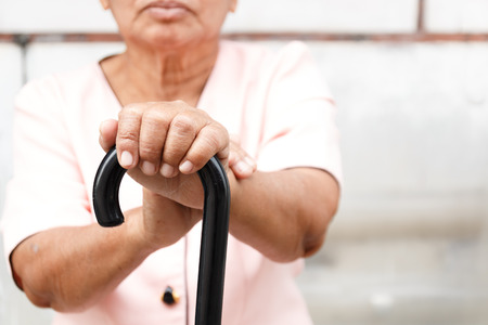 Close up of the old hands of an Asian woman holding a walking stick