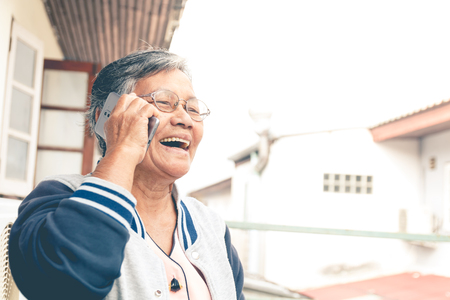 close up old asian woman with glassed use smartphone