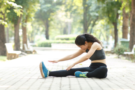 beauty asian with black sportwear stretching in park and natural blurred on background