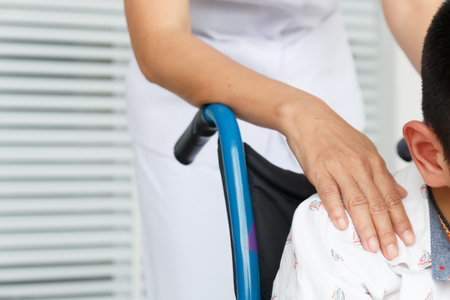 close up hand of nurse holding wheelchair with child autistic