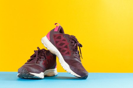 close up woman running shoes on blue yoga mat and yellow background Stock fotó
