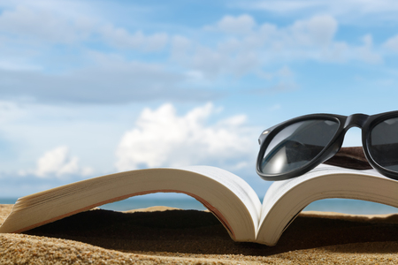 close up book and glasses on sand of beach on blur beautiful sky background, summer concept Stock fotó