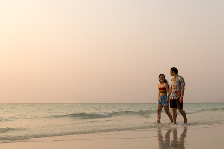couple asian man and woman walking on the beach silhouette at sunset