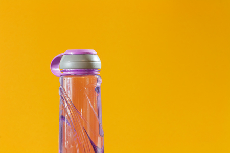 close up purple bottle of water on yellow background