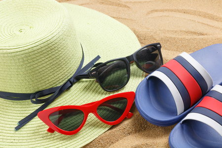 close up hat and red glasses and sunblock on sand of beach, summer concept Stock fotó
