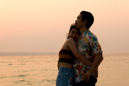 couple asian man and woman hugging on the beach silhouette at sunset