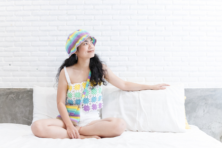 close up beauty asian woman funny moment on bed and white room with colorful knitwear
