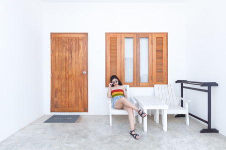 beauty asian woman sitting in front of room at beautiful resort place