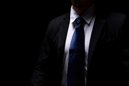 close upsmart businessman with black suit in dark concept