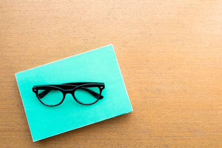 black glasses on green book on wooden of table background near window, education and reading concept