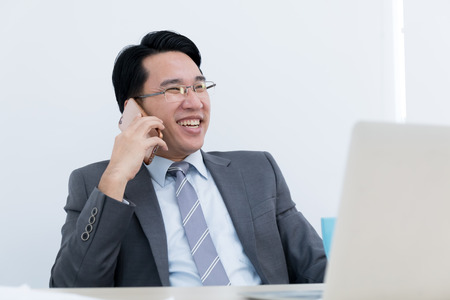 asian business man sitting celebration in office and use smartphone, success concept