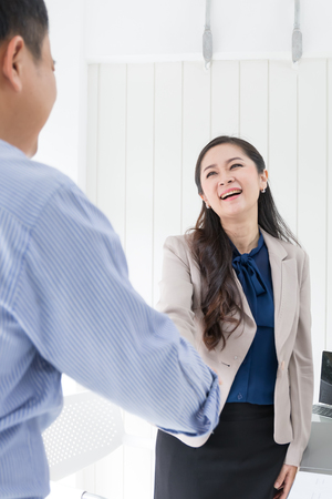 happy asian business man and woman shaking hands in office, successful or deal concept