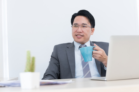 asian business man sitting in office and holding a cup of coffee relaxation in break time Stock fotó