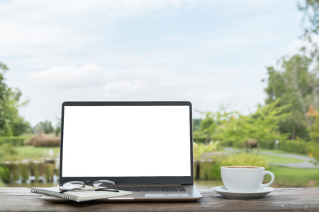 modern laptop black screen open and white cup and glasses on wooden table on outdoor natural and sky background