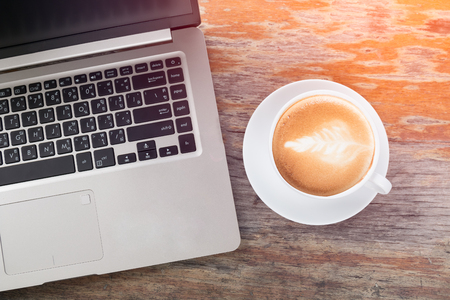 laptop and white cup of latte art on wooden table with light effect and vintage tone Stock fotó