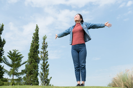 asian beauty woman with red shirt and jean jacket standing on green field and blue sky on background