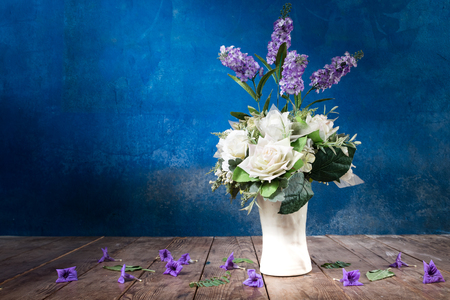 purple and white flowers in white vase on wooden ground