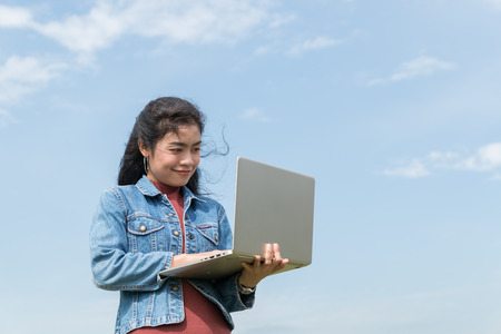 beauty asian woman with jean jacket  holding laptop on blue sky background Stock fotó