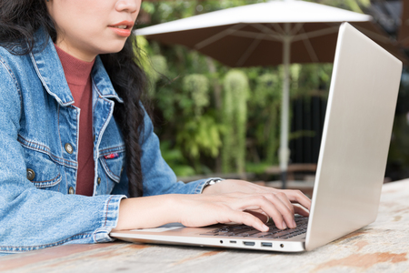 close up hand of business asian woman typing at laptop keyboard on outdoor, relaxation concept