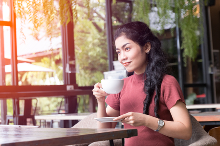beauty asian woman sitting holding white cup of latte with her hand in coffee shop, light effect and vintage tone