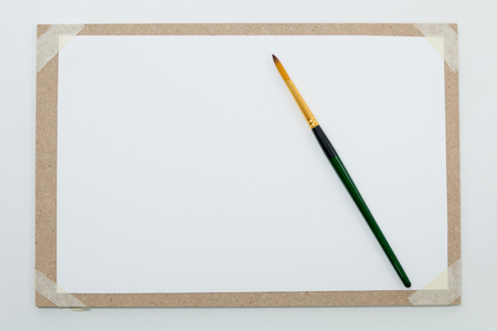 paintbrush on empty white paper with paperboard for background