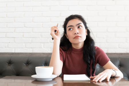 beauty asian woman sitting at leather chair and thinking in coffee shop on white background