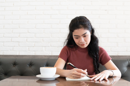beauty asian woman sitting at leather chair and writing note in coffee shop on white background