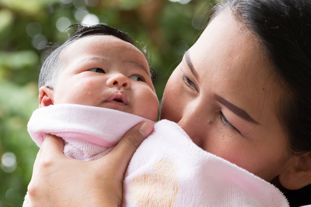 asian mother holding newborn daugther and natural blur on background