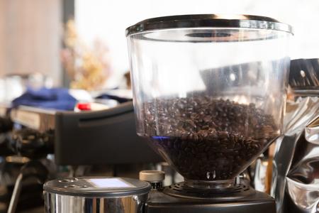fresh coffee seed in machine prepare to make powder in bowl