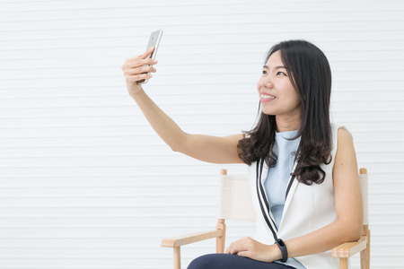 asian woman sitting at chair and use smartphone to selfie