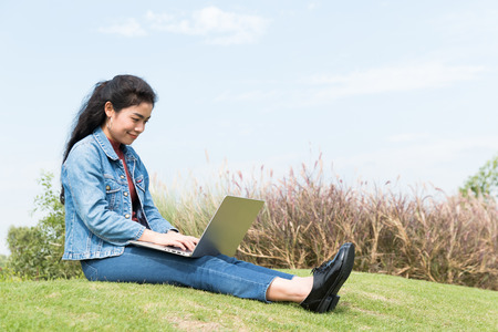 beauty asian woman with jean jacket sitting at green field and holding laptop on blue sky background