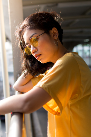 beauty asian woman with yellow wear and glasses in city Stock fotó