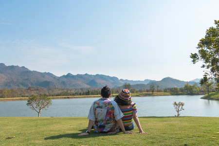 couple asian man and woman with colorful clothes and sit at green grass field on beatiful nature at background