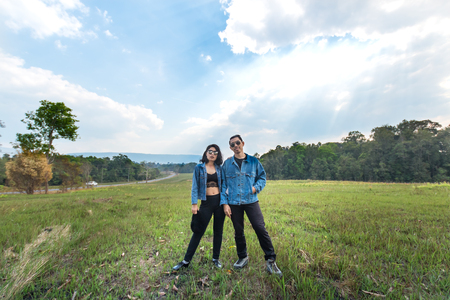 couple asian man and woman with jean jacket on green natural field and blue sky on background