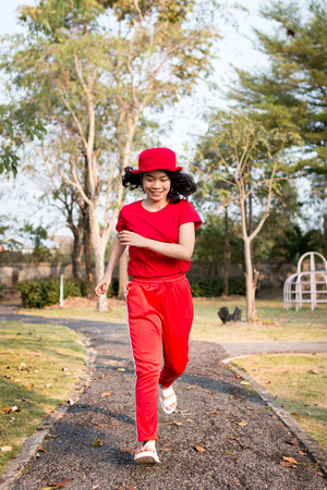 beauty asian woman with red clothes haooiness playing in playground