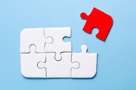 close up white jigsaw on blue color background and one part is red out of group with concept Stock fotó