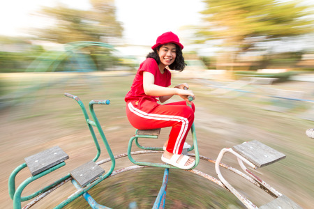 beauty asian woman with red clothes haooiness playing in playground with motionblur