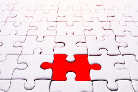 close up pattern of white jigsaw and one part is red for concept background Standard-Bild - 119600635